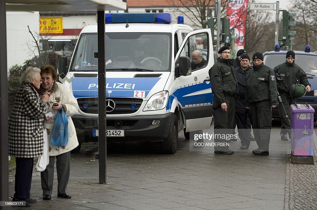 Two ladies chat at a bus shelter as police officers take up poitions during a demonstration in the Rudow neighborhood of Berlin on November 24, 2012.