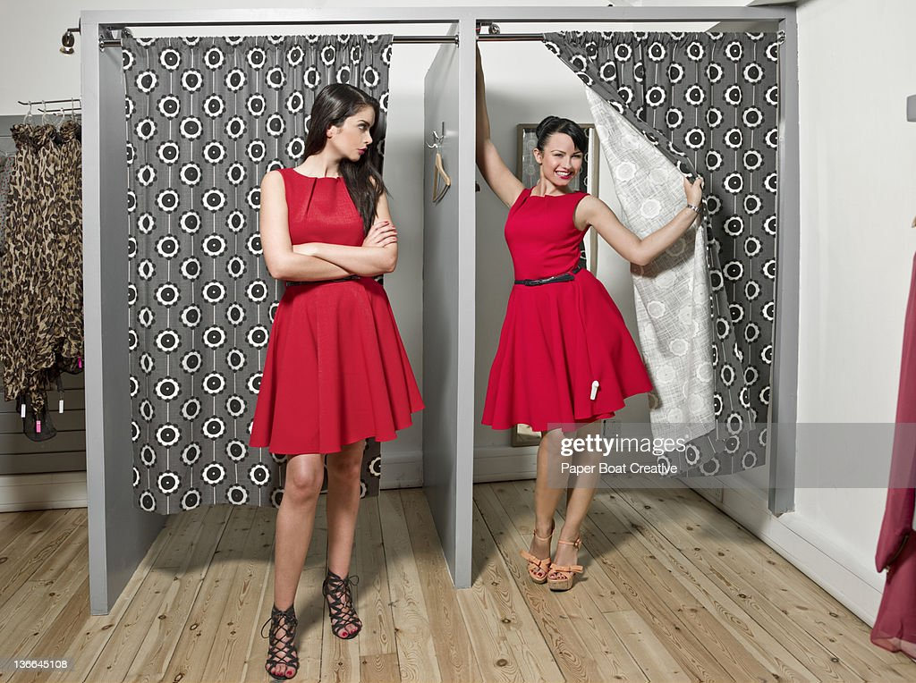 two ladies coming out with the same red dress : Stock Photo