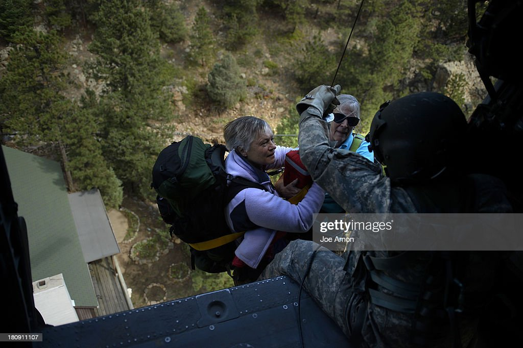 Two ladies have a first look at Sgt 1st class Keith Bart as they are hoisted into a UH-60 Black Hawk near Jamestown during search and rescue flight with members of the 2-4 GSAB with the 4th ID of Fort Carson September 17, 2013 Boulder, CO.