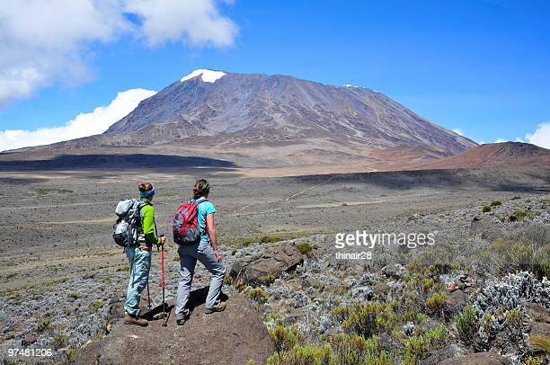 Two ladies hiking Mt Kilimanjaro on a sunny clear day