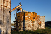 Two large tanks with peeling paint on green grass with clear blue sky