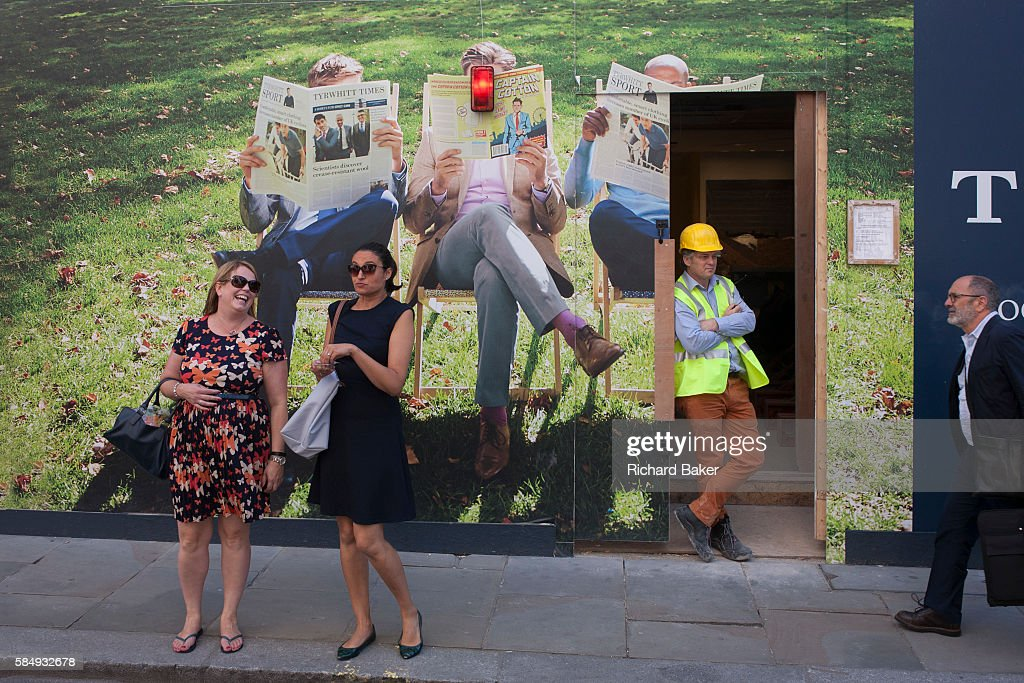 Two laughing women wait to cross Jermyn Street in front of a construction hoarding for fashion brand Charles Tyrwhitt on 6th July 2016 in London...