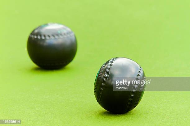 Two lawn bowling balls on a green background