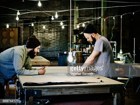 Two leatherworkers discussing product design