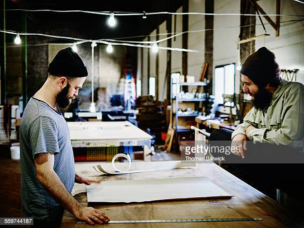 Two leatherworkers standing at table in workshop