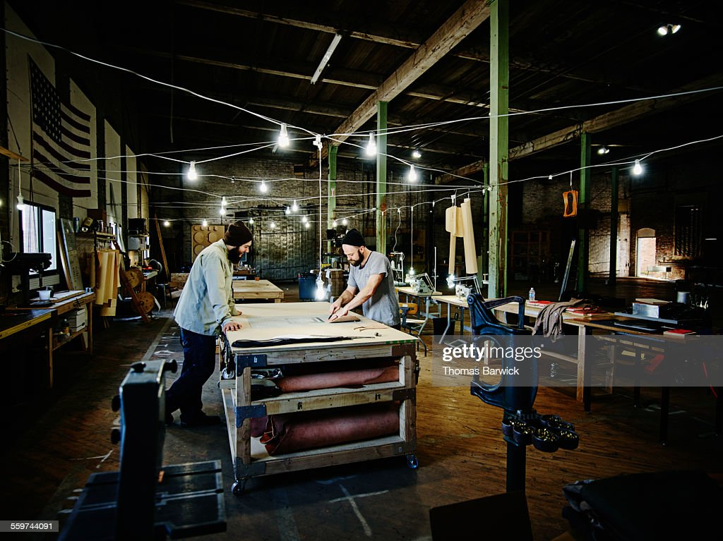 Two leatherworkers working on prototype design : Stock Photo