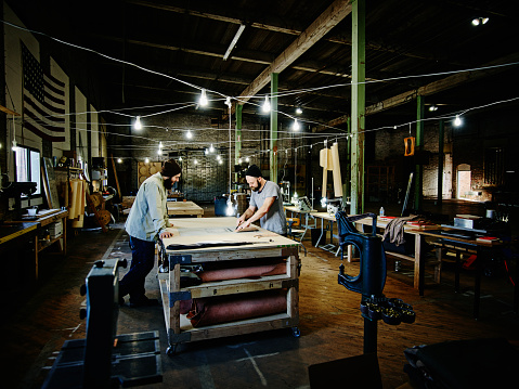 Two leatherworkers working on prototype design
