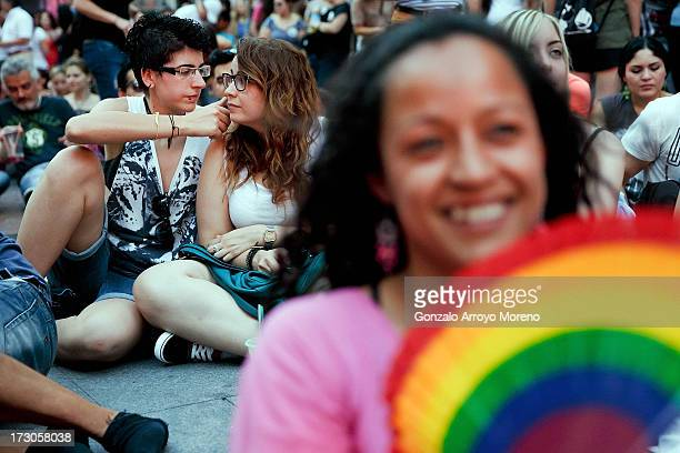 Two lesbian women sit at the Chueca Square stage during the Madrid Gay Pride Festival 2013 on July 5 2013 in Madrid Spain According to a new Pew...
