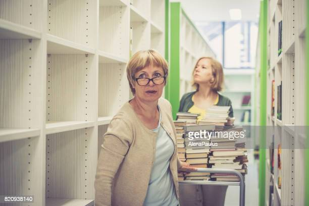 Two librarian women editing, sorting and renewing the new library - books on cart
