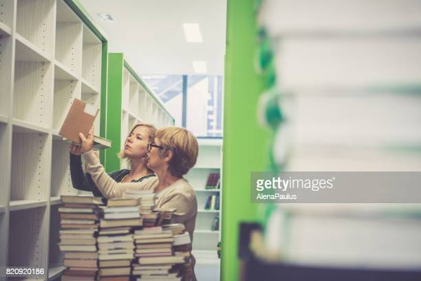 Two librarian women editing, sorting and renewing the new library - holding books