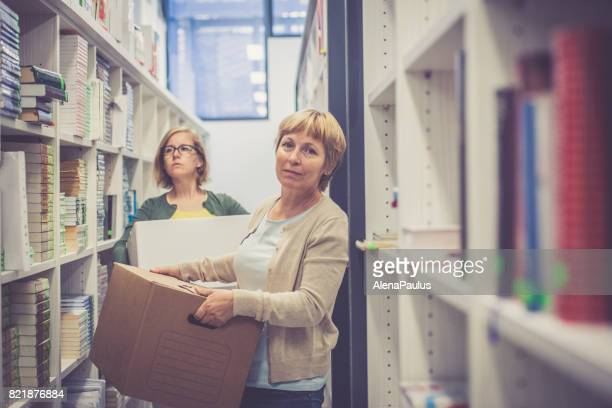 Two librarian women editing, sorting and renewing the new library - holding boxes with books