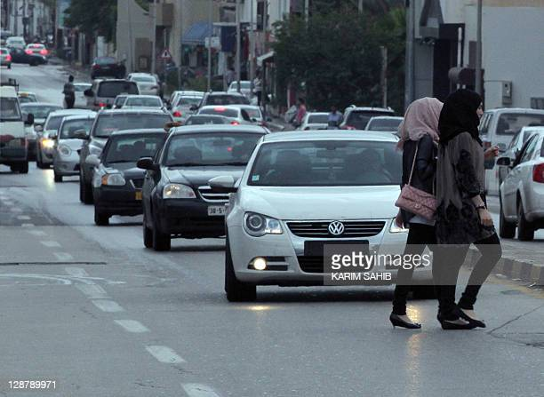 Two Libyan women cross the road as traffic drives along a main thoroughfare in Tripoli on October 8 weeks after the capital fell from former...