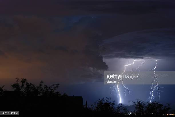 Two lightning bolts illuminating a cloudy sky at sunset