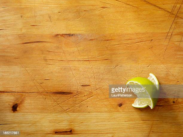 Two lime wedges on a wooden cutting board