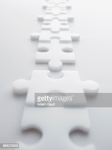 Two lines of separated interlocking puzzle pieces : Stock Photo