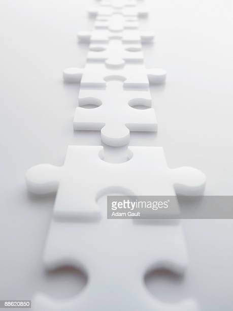 Two lines of separated interlocking puzzle pieces
