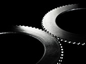 Two linked steel gear / cogs on black background