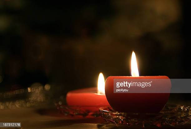 Two lit red candles on a table