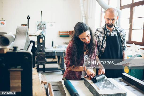 Two lithograph workers creating new pattern at printing house