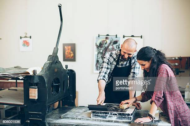 Two lithography workers using roller and printing press