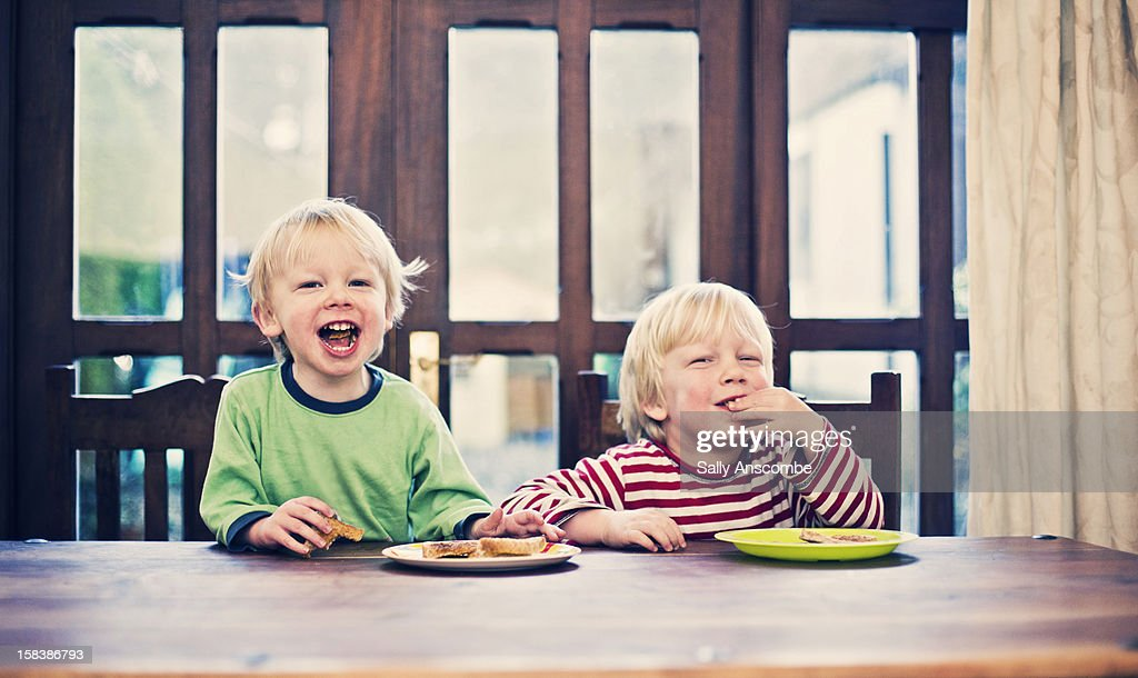 Two little boys eating toast for breakfast : Stock Photo