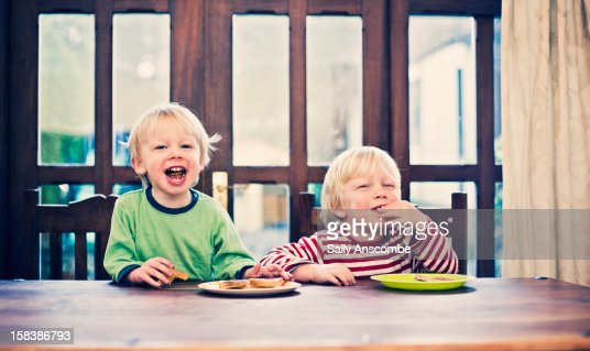 Two little boys eating toast for breakfast