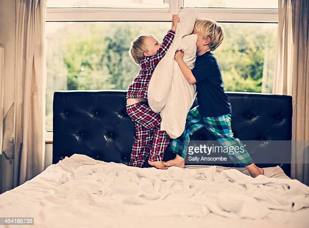 Two little boys having a pillow fight