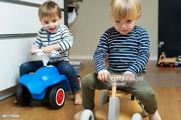 Two little boys playing at home with toy cars