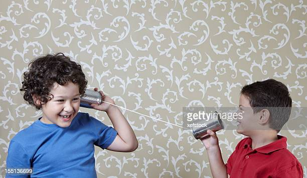 Two little boys playing with a tin can telephone