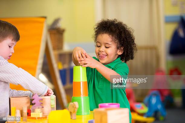 Two little boys playing with building blocks in a nursery