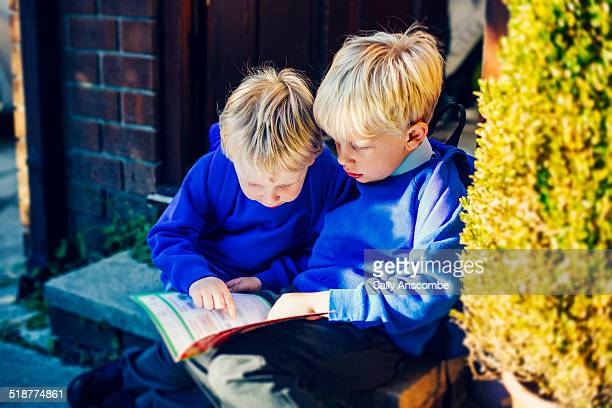 Two little boys reading a school book