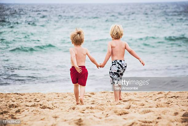Two little boys running to the sea