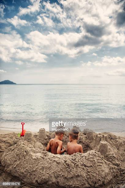 Two little boys sitting in a sandcastle on the beach