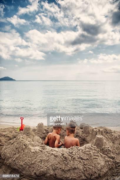 Deux petits garçons assis dans un château de sable sur la plage