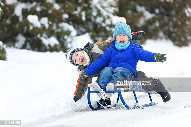 Two Little Boys Sledding On Snow