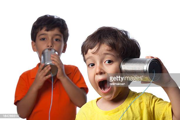 Two Little Boys Talking And Communicating On Tin Can Phone
