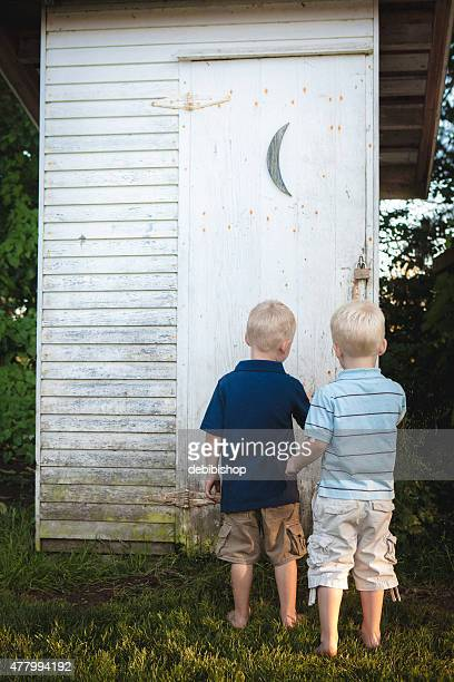 Two little boys waiting to enter outhouse to go potty