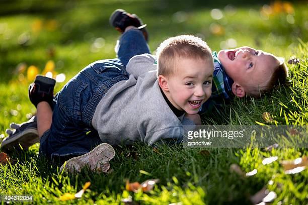 Zwei kleine Jungen Ringen auf Gras in einem Park