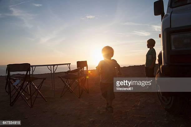 Two little brother beside a caravoan at backlight