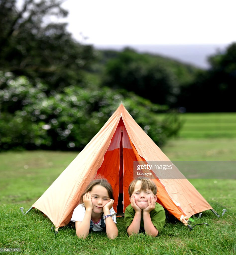 Two Little Children Looking Lying in Entrance of Small Tent : Stock Photo