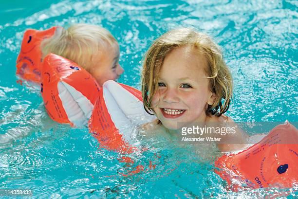 two little children wearing water wings swimming in pool