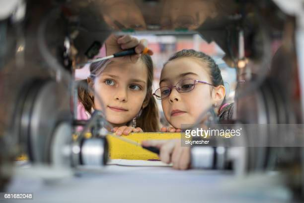 Two little engineers working in team while repairing a robot.