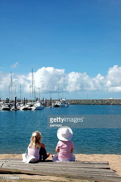 Two little girls at the beach looking at boats