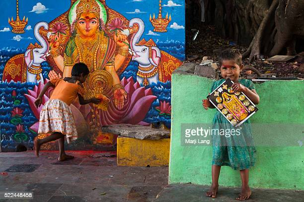 Two little girls by a holy tree and a mural with the goddess Lakshmi near Sri Venkateswara swami temple in Tirumala Andhra Pradesh India