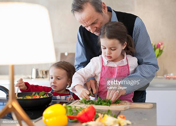 two little girls cooking with grandfather