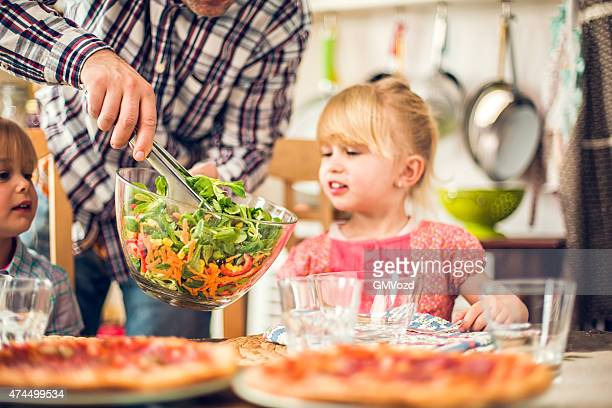 Two Little Girls Eating Pizza with Fresh Salad