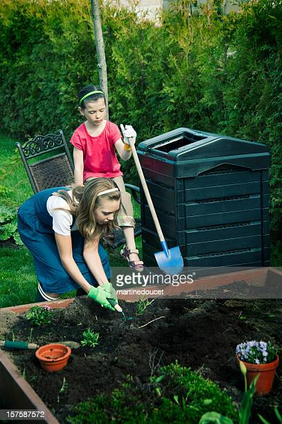 Two little girls gardening and composting in the garden.