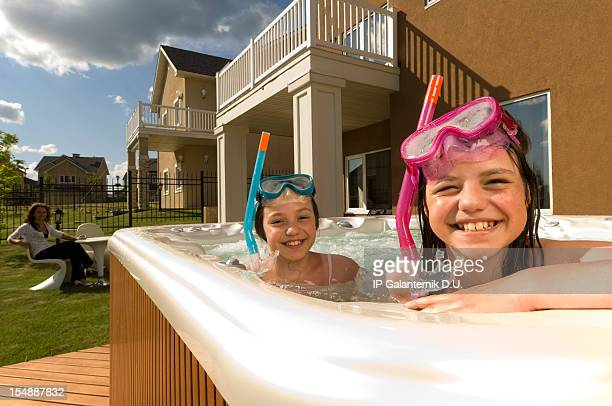 Two little girls have fun in small swimming pool