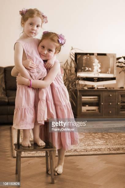 Two Little Girls Hugging in Living Room