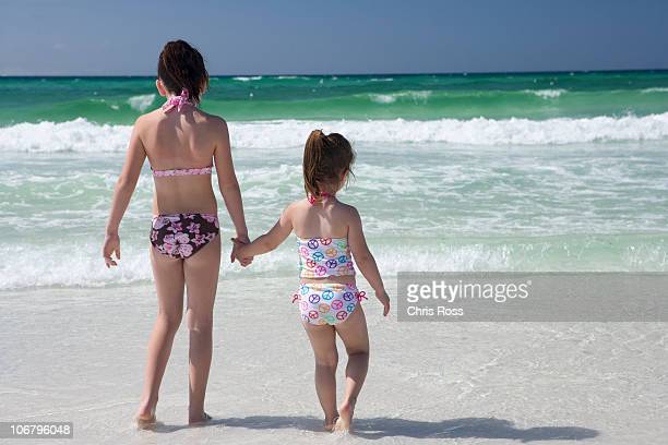 Two little girls in bikinis are holding hands at shoreline with the ocean in the background.